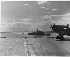 """The battleship Washington (BB-56) at anchor at Scapa Flow, Scotland, as seen from the flight deck of the aircraft carrier Wasp (CV-7). Note the barrage balloons overhead."""
