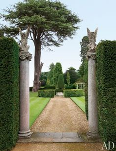 Stone columns crowned with 19th-century statues flank a gravel walk in the gardens | archdigest.com