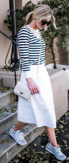 casual outfit inspiration grafic top + white skirt + bag + sneakers