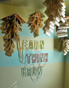 DIY Anthrofied Book Mobiles and Nail Yarn Wrapped Letters via Anthromollogies. {I really love how the letters are directly on the wall, but instead of making a million holes in my wall, I'd opt to do this on a weathered board}