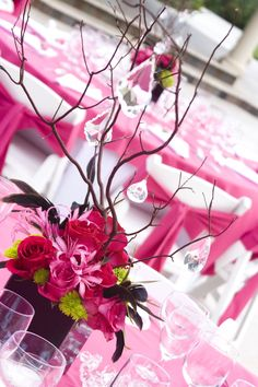 Custom Centerpiece. Colors were black, hot pink and lime green so we did black vase with hot pink roses and nerines, lime green button mums, black feathers and the manzanita branch with cystals hangingvendors: Simply That Flowers