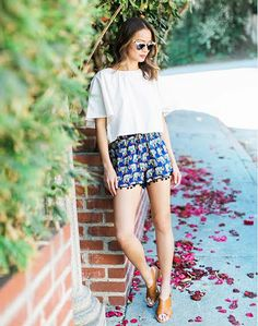 Jamie Chung wears a white crop top, printed shorts, clubmaster sunglasses, and tan leather sandals