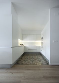 líneas minimalistas y en blanco, con todos los electrodomésticos integrados y líneas de luces LED ocultas