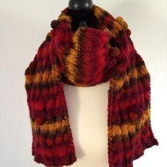 Ein herrlich warmer und weicher Herbstschal in leuchtenden rot-senf Tönen mit einem aufwendigen Zopf- Noppenmuster. Der Schal hat eine Länge von ca. 2 m und ist 17 cm breit.