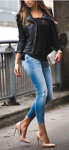 Black leather jacket over black top with blue jeans.