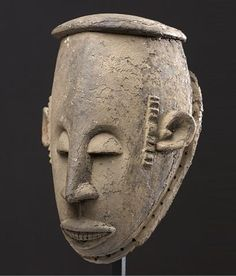 Dance Mask. Ibo, Nigeria, 19th Century. This mask is a superb example of Nigerian art. With it's strong brow jutting downward to a sharp nose and finely carved mouth , this mask has great presence. This mask possesses an incredible patina with layers of encrustation. The combination of surface and carving quality make this one of the oldest and best Ibo masks I have ever handled. Some loss to the side attachment rim; but otherwise excellent condition.  The mask stands 11 inches in height.