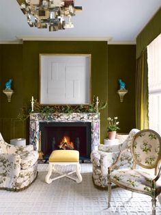 """It had been largely untouched since the 1950s when, in 2010, Veere Grenney—former director of the renowned British design firm Colefax and Fowler—bought the house from a friend who had inherited it from his great-aunt. """"It's Regency, with a stone staircase, which makes it particularly charming,"""" Grenney says. Rich, mossy velvet from Alton-Brooke on the walls and for the curtains evokes a woodland setting in the drawing room. 18th-century English chair in Colefax and Fowler chintz; mantel, Jamb;"""