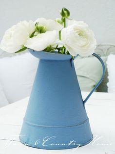 White flowers in blue enamel jug for table in back yard