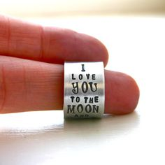 This wide ring has an important message: I Love You To The Moon and Back. This custom ring can be stamped with any name, word, or short phrase.  Shown