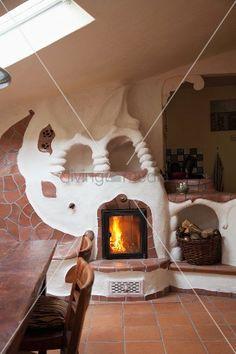 In organischen Formen modellierter Kachelofen mit Terracottafliesen in der offenen Wohnküche einer urigen Ferienwohnung