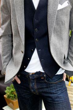 grey herringbone blazer / white pocket square / dark blue dogtooth waistcoat / buttoned white tee / dark denim