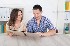 Happy Couple Looking At Photo Album ...  album, attractive, beautiful, book, brunette, casual, cheerful, couple, emotion, family, female, folder, girl, gorgeous, guy, handsome, happy, holding, home, husband, interest, joy, lady, look, love, lover, male, man, memories, people, person, photo, photobook, photography, pictures, pretty, relationship, school, sitting, smile, smiling, table, together, togetherness, university, wall, watching, wife, woman, yearbook