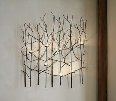 Lit with votive candles, this nature-inspired wall art candle holder flickers a magical forest of shadowy branches. Constructed of iron, this eye-catching piece captures the delicate tracery of tree twigs, interspersed with cups and glass votive holders. This handcrafted stunner creates a magical, artful ambience in the dining room, over a sofa or in the entryway.