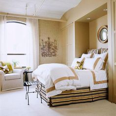 Nice Niche: The recessed space between two small closets in this room offered the perfect place to fit a bed. A creamy latte paint covers the walls and camouflages a brick wall. Stripes add a contemporary vibe, as do the polka-dot accent pillows.