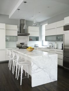 marble waterfall island + glass pendants in modern white kitchen