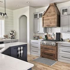 Range + hood, light gray wal cabinetry + dark gray island