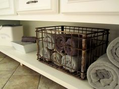 Good idea, I actually bought cheap wicker laundry baskets for all my bathrooms and roll all the towels in them, and add a can of room freshener!