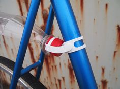 A while ago, I saw a guy clamping an old plastic bottle between the seat stays of his bike, to use it as a fender. It doesn't look very stable but it was a great idea anyway!  This 3d printed mount works with most plastic bottles, like Coke, Evian ect. You can just clip it on your bike - no glue or screws needed!  The bottle-fender-mount works nice on old steel bike racing frames.  Manufactured via Shapeways 3D printing service.