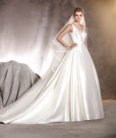 The ALCOBA wedding dress is a surprising model in mikado with a bateau neckline a low-cut, provocative back in lace with embroidery and gemstones.