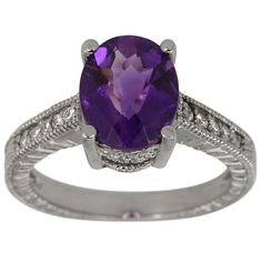 Large Oval Amethyst In 14K White Gold Antique Diamond Ring -  The oval amethyst and round brilliant diamonds weigh a total of 2.68ct.    There is a deep purple amethyst in a 14K white gold vintage setting. A filigree-adorned gallery sits underneath the stone, and the shanks are also embellished with filigree, as well as prong-set diamonds. In addition, the shank is engraved with ornate Victorian-inspired ornamentation.    At Dacarli emphasis is placed on design, quality, and modern…