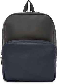 Grained leather backpack in dark grey and navy colorblock. Textile-trimmed grab handle and shoulder straps affixed at top. Gunmetal-tone hardware. Two-way zipper at main compartment opening. Zippered patch pocket at bag face. Zip pocket and patch pockets at lined interior. Tonal stitching. Approx. 12