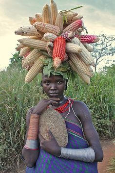 the girl is beautiful, the corn is beautiful, and the harvest balancing atop her head is a beautiful image