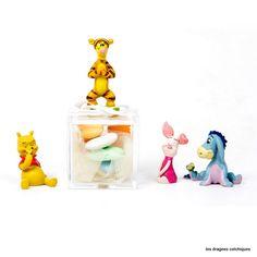 Porte dragées en plexiglas rempli de dragées et sujet winnie, tigrou, bourriquet thème Disney.