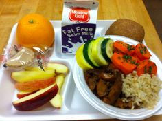 Teriyaki Chicken Rice Bowl; brown rice, steamed fresh carrots, zucchini, yellow squash and Teriyaki chicken. Served with fresh local apple slices, whole grain roll, ice cold milk, an orange, and a fortune cookie.