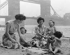 Two women take their children for a picnic on Tower Beach, an artificial beach near Tower Bridge on the River Thames, London | British summer in the 1950s | Galleries | Pics | Daily Express