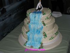 """Waterfall wedding - The bride wanted a waterfall wedding cake because he hubby to be loved fishing. She had the bride dragging the groom cake topper and there was a fishing pole with a """"fish"""" hanging over the waterfall."""