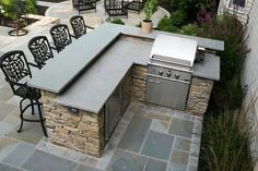 Outdoor Fieldstone kitchen featuring raised stone bar counter and grill incorporated into a backyard patio design. Outdoor Kitchen Countertops, Outdoor Kitchen Bars, Backyard Kitchen, Outdoor Kitchen Design, Backyard Barbeque, Outdoor Bars, Outdoor Grill Area, Outdoor Grill Station, Simple Outdoor Kitchen