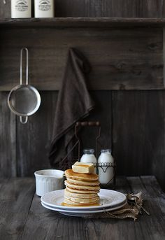A towering stack of pancakes with a heaping amount of fresh butter and some cold milk in a glass bottle. Add a thick pour of some golden maple syrup and it sounds like a breakfast made in heaven. Or, a breakfast made in a quaint, country kitchen.