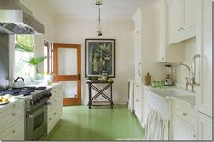 white kitchen with green painted wood floors