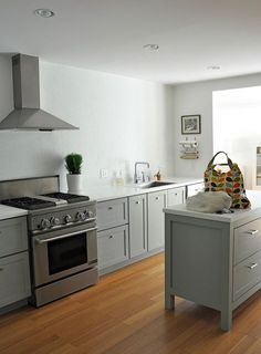 greyish cupboards, wooden floors, white walls