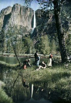 California - A family on the bank of a water body with a view of a cliff waterfall, Yosemite. Photo from National Geographic's image collection.