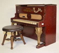 circa late nineteenth century to 1920s Fancy Schoenhut upright toy piano with metal legs, candlestick holders (only 1 still surviving), and fabric window.