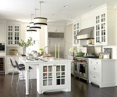 Your cookbooks should be conveniently located without contributing clutter to work areas. Here's a great solution: At the end of this kitchen island, a built-in bookshelf keeps cookbooks off the counter and in one spill-resistant space. Besides giving the cook quick access to recipes, the bookshelf provides warmth and a pop of color to the all-white, fairly formal kitchen.