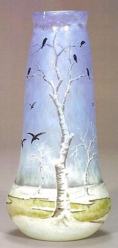 "A supreme Daum Nancy cameo vase featuring a landscape shrouded in snow. A yellow river meanders through the isolated setting as a flock of sixteen black birds are in flight or have just perched in barren birch trees, gathering for the evening roost. This tranquil setting is silhouetted against a beautiful mottled sky of blue. Enamel signed ""Daum Nancy"" with the croix of Lorraine."