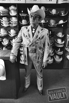 Nudie Cohn @ Nudie's Rodeo Tailor (Hollywood, CA) Jun 28, 1969. Nudie Cohn, on the cover of Rolling Stone Magazine No. 36, was tailor to the celebrities. His signature suits were covered with rhinestones and appliques, often with distinctive themes. His suit for Gram Parsons featured cannabis leaves, pill bottles, and naked women. For Elvis he designed and produced a 10,000 dollar gold lame suit. -Baron Wolman http://www.wolfgangsvault.com/nudie-cohen/photography/fine-art-print/BWP0063.html