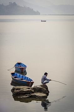 A man fishing on Phewa Tal (Phewa Lake), Pokhara, Nepal, Asia