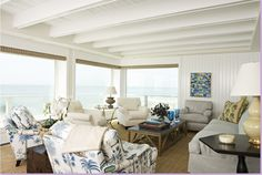 Blues and white, seagrass matting over dark hardwood floors, wood paneling, Michael Smith fabric on the sofa's pillow. Dark hardwood furniture. Calm, serene, and casual - everything you would expect a beach house to be