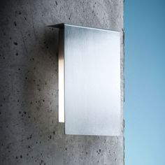 Corrubedo (lighting): Wall lamp for outdoor. Structure in satin stainless steel. Diffuser in white opal polycarbonate. Protection screen in transparent borosilicate glass. Diffused light emission upwards or downwards in accordance to the installation. (designer: David Chipperfield | year: 2008) - More @ www.fontanaarte.com #fontanaarte #light #lamp