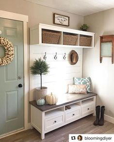 Beautiful farmhouse style entry way. Love how soft everything feels with the color scheme and the pops of teal with the door and matching throw pillow. The mini potted tree is a cute touch to the bench.