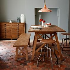 Mixing clean lines with rustic pieces will keep dining rooms from looking cold. Wooden benches are a great space saver and will complement the sturdy lines of the chunky table too. Rustic country-style stools are a great option for giving extra seating space at dinner parties, without overwhelming the look. The hexagonal terracotta floor tiles will make a delightful contrast to the perfectly painted grey walls and wooden table and chairs.