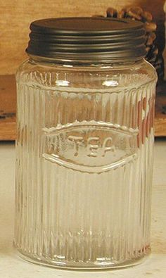 "Hoosier Glass Tea Jar. 4.25"" wide and 7"" high. The word ""Tea"" is molded on the jar. Rustic brown metal lid is included."