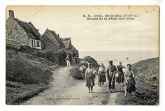 Agrandir l'image Carte postale en noir et blanc d'un chemin en terre battue menant à la plage. À gauche, se trouvent de petites maisons en hauteur. Un groupe de cinq pêcheurs munis de grands bâtons et de seaux remonte de la plage.