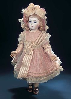 """Marks: 9. Comments: Emile Jumeau,circa 1882,an early model of the beloved bebe designed by French sculptor Carrier-Belleuse under commission from Jumeau. Value Points: dramatically-deep paperweight eyes contrast beautifully the pale complexion,lovely wig,original early Jumeau body,and wearing a superb embroidered tulle dress with lace and silk trim,undergarments,fancy bonnet,worn brown leather shoes signed """"Bebe Jumeau Depose 9""""."""
