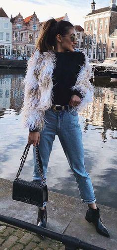 10 formas estilosas de usar pelinhos no inverno. Casaco faux fur, blusa de manga preta, cinto western, mom jeans, ankle boot preta de bico fino