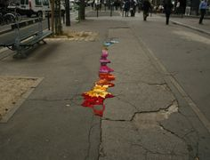 """Street Repairs""  Seeing a world full of cracks? Fill them in! In cities continuously mid-crumble,  street repairs offer an artistic alternative to long awaiting concrete cracks.  One options is knitting/gluing colourful yarn, such as the artist below!"