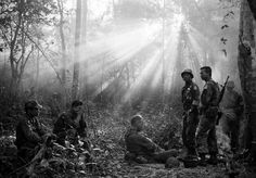 In this January 1965 file photo taken by Associated Press photographer Horst Faas, the sun breaks through dense jungle foliage around the embattled town of Binh Gia, 40 miles east of Saigon, as South Vietnamese troops, joined by U.S. advisers, rest after a cold, damp and tense night of waiting in an ambush position for a Viet Cong attack that didn't come.